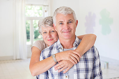 Older couple hugging in living space  - p1023m962418f von Martin Barraud
