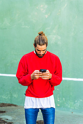 Bearded young man with dyed hair wearing red sweatshirt  in front of green wall using cell phone - p300m2159943 by VITTA GALLERY