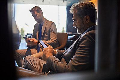 Two businessmen using smartphones in hotel lobby - p300m2171391 by Zeljko Dangubic