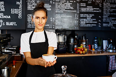 Portrait of smiling waitress giving coffee at cafe - p300m2225076 by Bartek Szewczyk