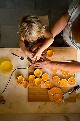 Boy making orange juice with father - p312m2162050 by Maritha Estvall