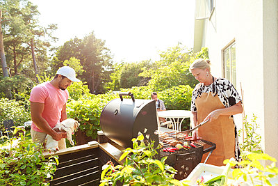 Couple in garden, woman preparing food on barbecue - p312m2237114 by Phia Bergdahl