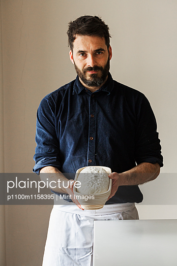 Baker holding a freshly baked loaf of white bread in a rattan proofing basket. - p1100m1158395 by Mint Images