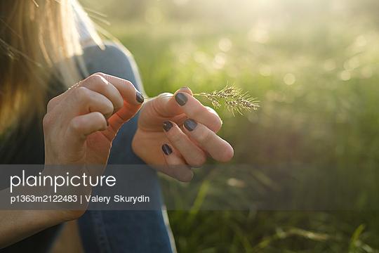 Woman holding grass stalk - p1363m2122483 by Valery Skurydin