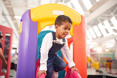 Smiling boy playing on slide - p1023m2016970 by Trevor Adeline