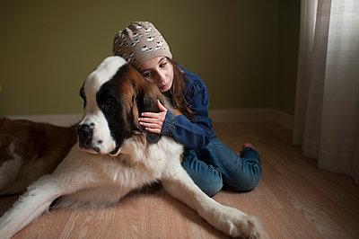 Girl embracing Saint Bernard while sitting on floor at home - p1166m1414634 by Cavan Images