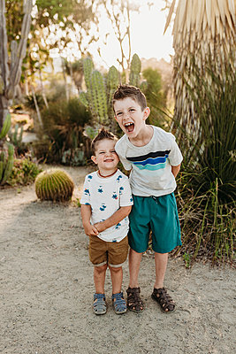 Full body view of elementary aged boy and toddler brother laughinghi - p1166m2136649 by Cavan Images