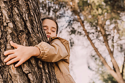 Cute girl with eyes closed hugging tree at park - p300m2225479 by Eloisa Ramos