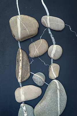 Pebbles with white line arranged on grey board - p300m965214f by Ophelia photography