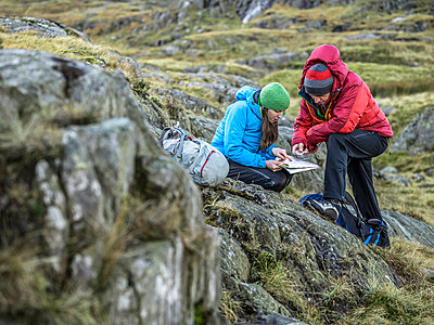 Hikers using map and compass - p429m765317 by Julian Love