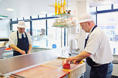 Caucasian butcher slicing meat behind counter in shop - p555m1410356 by Dave and Les Jacobs