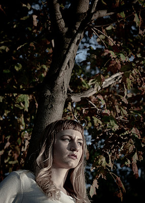 Young woman leaning against tree with autumn colours - p758m2222595 by L. Ajtay