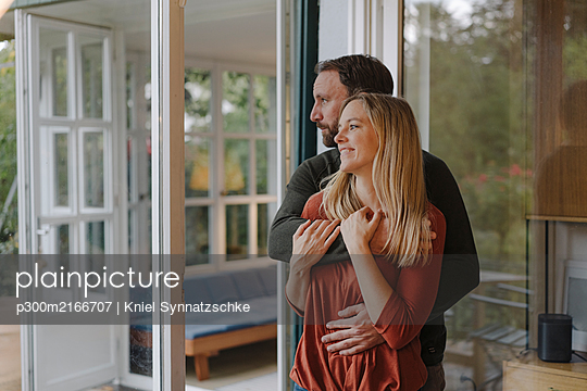Happy couple embracing in their comfortable home - p300m2166707 by Kniel Synnatzschke