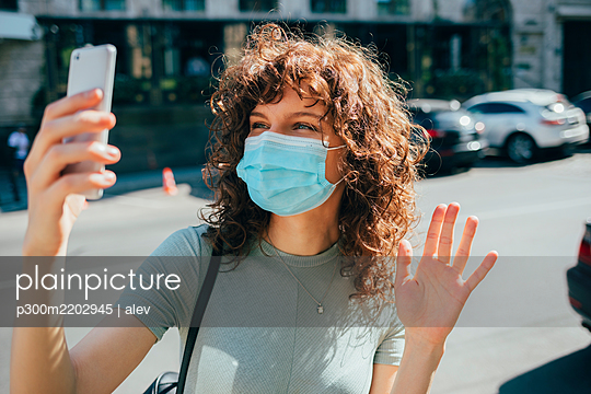 Woman wearing protective mask and using smartphone in city - p300m2202945 by alev