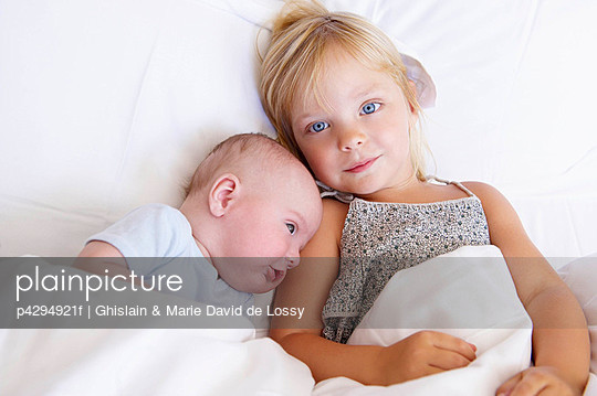 Girl with her baby brother in bed