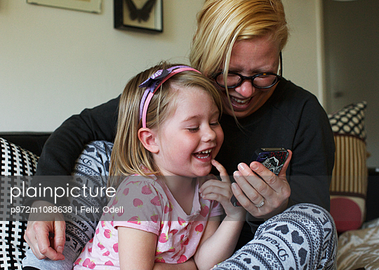 Mother and daughter using smartphone - p972m1088638 by Felix Odell