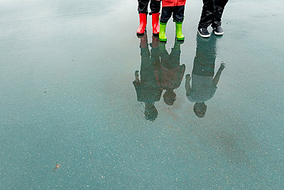 Low section of friends reflecting while standing on wet city street during rainy season - p1166m1485274 by Cavan Images
