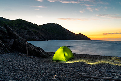 Spain, Catalonia, Costa Brava, green tent at stony beach in the evening - p300m2023783 by VITTA GALLERY