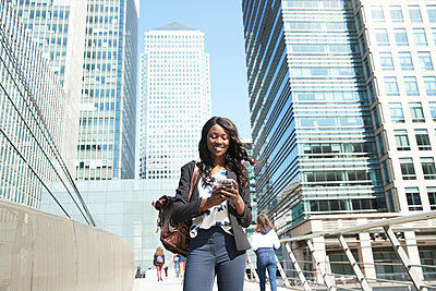 Businesswoman using mobile phone while standing in city - p300m2241621 by Pete Muller