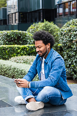 Stylish man listening music and using smart phone while sitting on retaining wall - p300m2243997 by NOVELLIMAGE