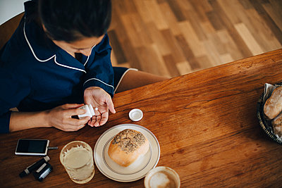 High angle view of woman taking medicine while having breakfast at table - p426m1537122 by Maskot