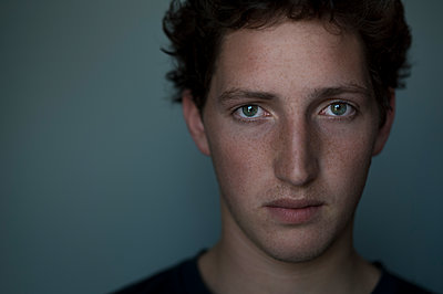 Young man with freckles - p552m1137990 by Leander Hopf