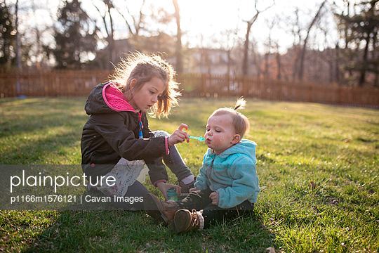 Sisters blowing bubbles while sitting on grassy field at park - p1166m1576121 by Cavan Images