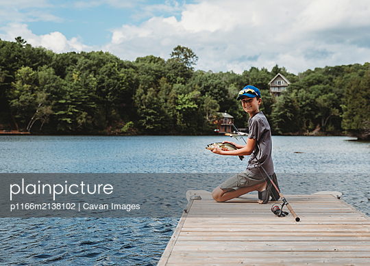 Boy holding a fish that he caught on the end of a dock on a lake. - p1166m2138102 by Cavan Images