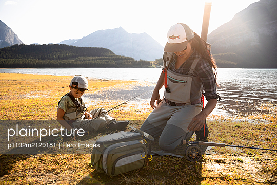Mother and son fly fishing at sunny lakeside - p1192m2129181 by Hero Images