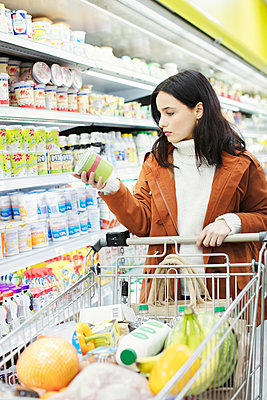 Woman reading label on container in supermarket - p1023m2187683 by Robert Daly