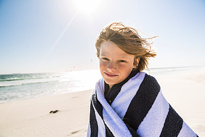 Portrait of smiling boy wrapped in a towel on the beach - p300m2167523 by Floco Images