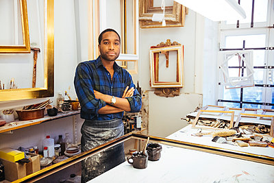 Portrait of confident young craftsman standing with arms crossed at workbench in framing workshop - p426m2089082 by Maskot
