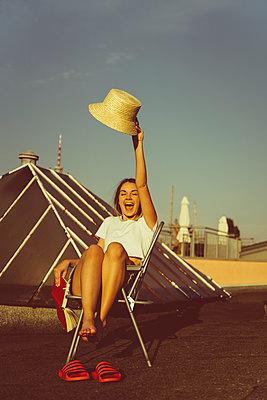 Junge Frau sitzt entspannt mit Buch auf Hausdach - p432m2260318 von mia takahara