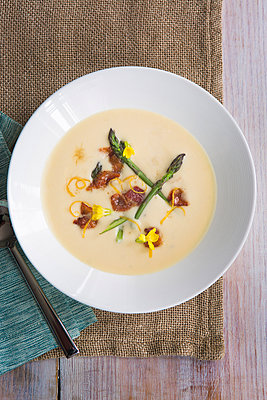 Overhead view of soup with asparagus and lemon zest garnish - p924m1030337f by Christopher Villano