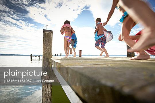 Kinder laufen über einen Steg, Starnberger See, Oberbayern, Bayern, Deutschland - p1316m1161067 von Jan Greune