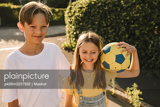 Smiling brother and sister with soccer ball on road during sunny day - p426m2237932 by Maskot