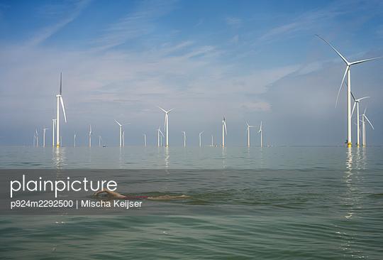 Netherlands, Friesland, Breezanddijk, Woman and girl swimming near wind turbines - p924m2292500 by Mischa Keijser