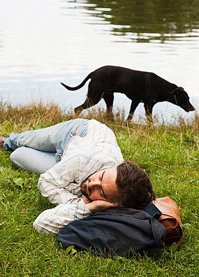 Mann schläft am Seeufer - p1008m1169999 von Valerie Schmidt