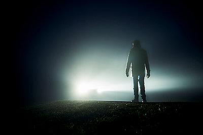 Mann vor Auto mit Scheinwerfern Im Gegenlicht im Nebel - p1312m2087535 von Axel Killian