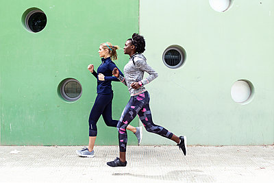 Two sporty young women running together in the city passing wall with round windows - p300m2083417 by Josep Suria