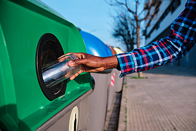 Man putting glass jar in recycling bin on footpath - p300m2273546 by Alvaro Gonzalez