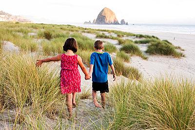 Caucasian children walking on beach - p555m1411257 by Adam Hester