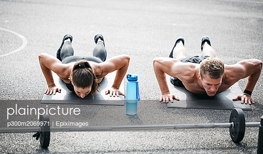 Sportive man and woman during pushups - p300m2069971 by Epiximages
