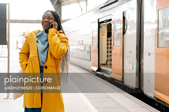 Portrait of smiling young woman on the phone standing on platform, Barcelona, Spain - p300m2166520 by COROIMAGE