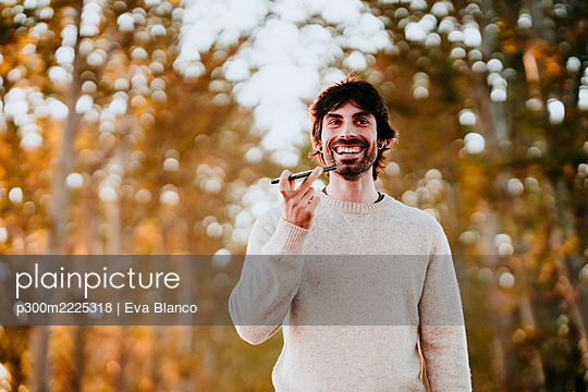 Smiling man talking on mobile phone while standing at forest - p300m2225318 by Eva Blanco