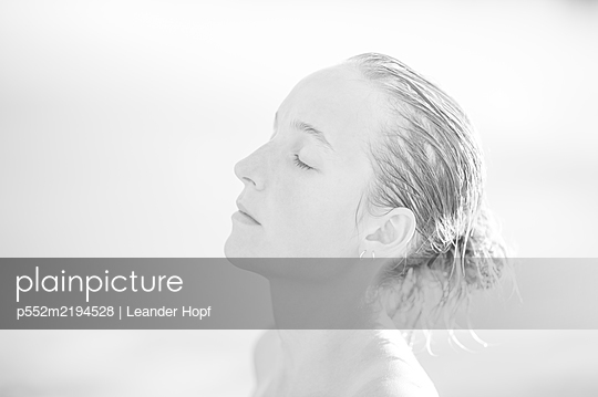 Portrait of young woman with wet hair, profile view - p552m2194528 by Leander Hopf