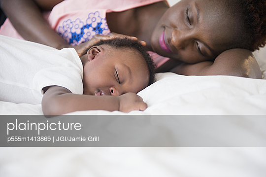 Black mother admiring sleeping son on bed - p555m1413869 by JGI/Jamie Grill