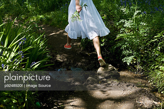 Woman walking in a garden - p9248920f by Image Source