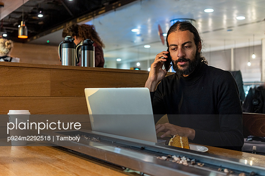 UK, London, Man using laptop and smart phone at airport cafe - p924m2292518 by Tamboly