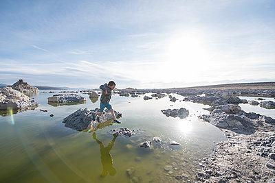 Boy jumping on Mono Lake rocks beside tufa towers, California, USA - p1424m1519351 by Aurora Premium